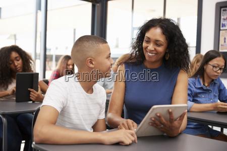 teacher helping teenage schoolboy with tablet