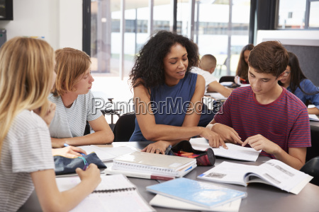 teacher studying school books in class