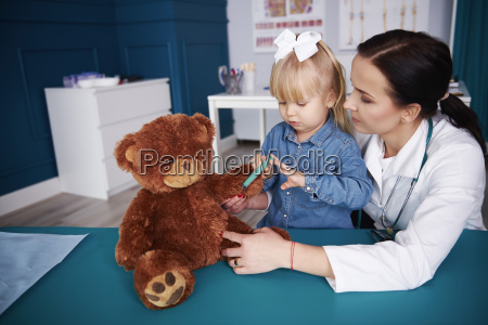 doctor and girl vaccinating teddy in