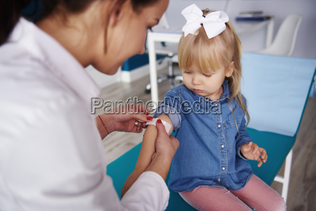 doctor applying band aid on girls