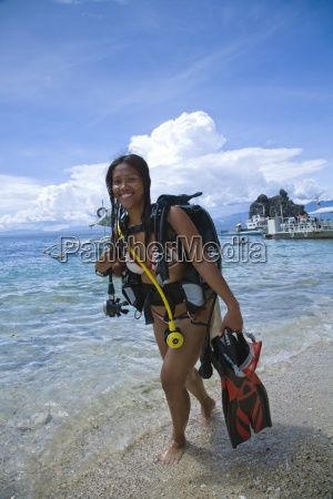 young woman with diving equipment standing