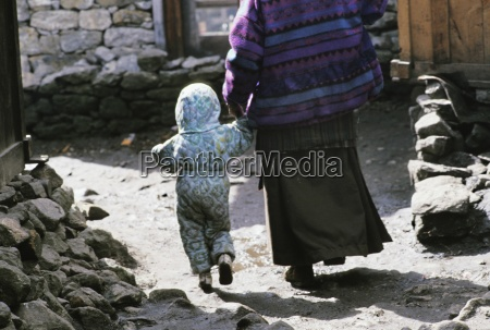 woman and small child holding hands