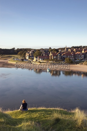 woman sitting on waters edge alnmouth