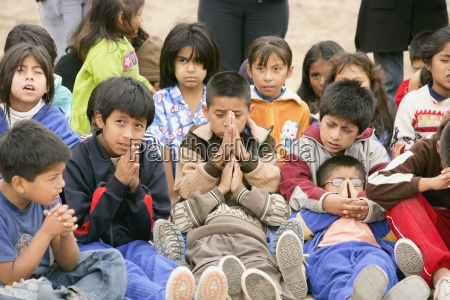 group of young children praying lima