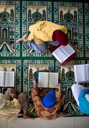 four people reading the koran indonesia