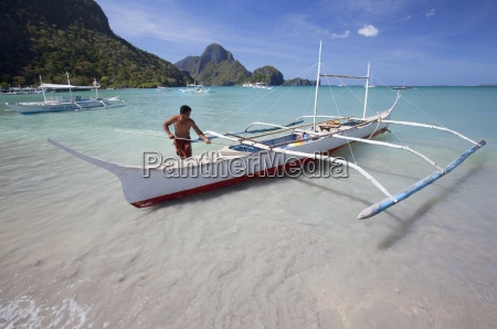 a man secures his wooden bangka