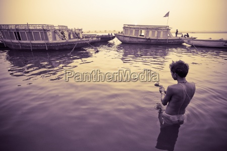 man swimming in harbor varanasi india
