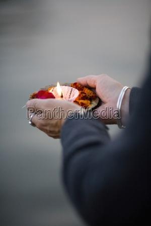 woman holding burning candle varanasi india