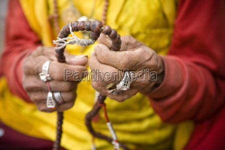 buddhist monk holding prayer beads boudhanath