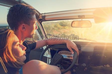 pareja en un coche al atardecer
