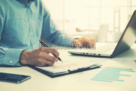 biznesmen analizujacy roczny raport biznesowy i