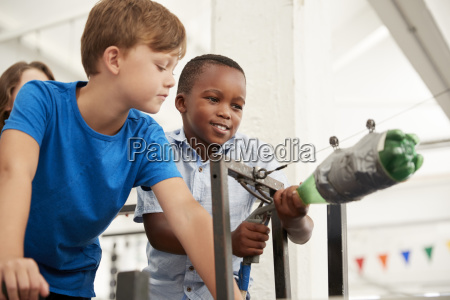 two schoolboys using air pressure rocket