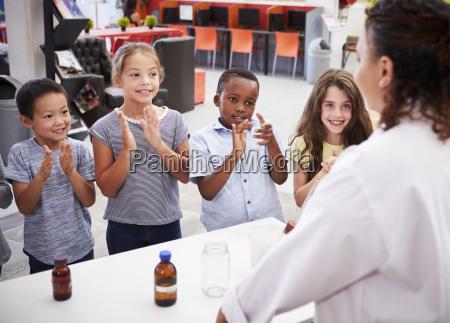 companyeros de clase aplaudiendo al maestro