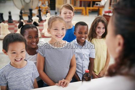 grupo de ninyos sonrientes escuchando al
