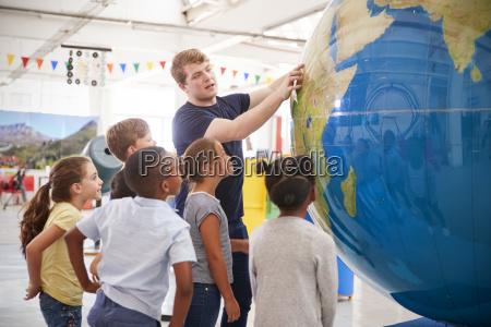 kids watch presentation with giant globe