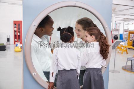 schoolgirls looking in a magnifying mirror