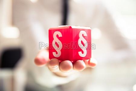 persona sosteniendo bloque cubico con simbolo