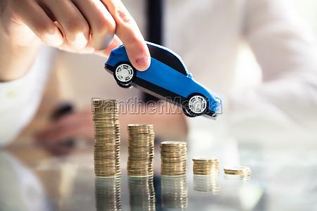 persona volando coche sobre monedas apiladas