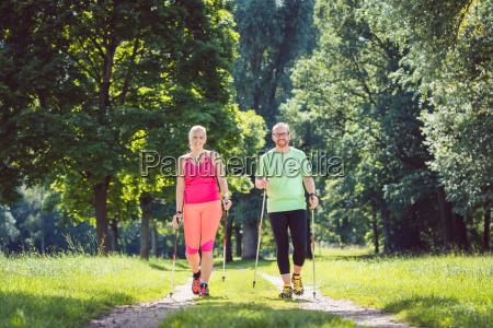 pareja haciendo nordic walking para el