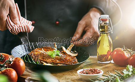 man holding black frying pan with