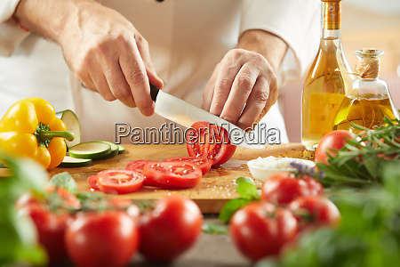 chef slicing fresh tomatoes for a