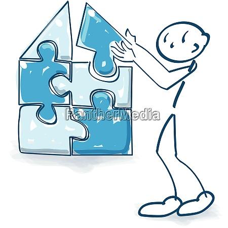 figura de palo construye una casa
