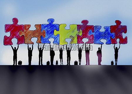 empresarios en una fila sosteniendo piezas