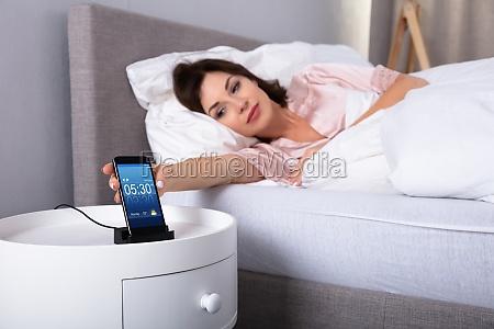 mujer dormitando alarma en el telefono