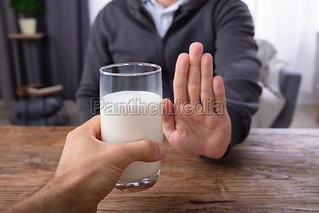 man refusing glass of milk offered