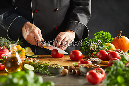 chef slicing salad ingredients in a