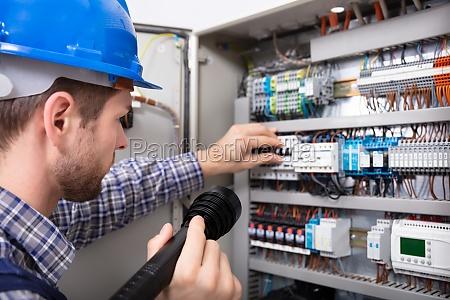 electricista examinando una caja de fusibles