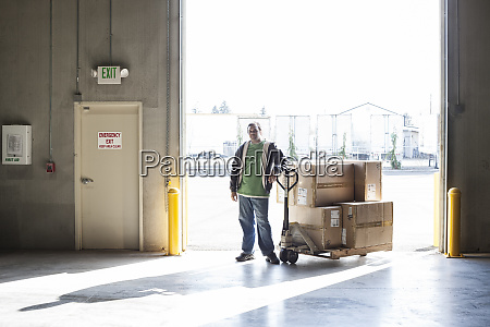 male warehouse worker standing next to