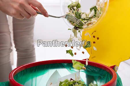 mujer tirando verduras en la papelera