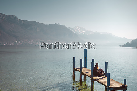 woman sitting on jetty on lakeshore