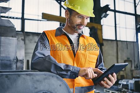 smiling man wearing protective workwear using