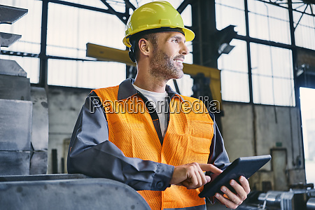 smiling man with tablet wearing protective