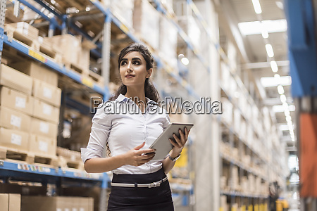 woman with tablet in factory storehouse