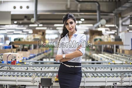 portrait of confident woman at conveyor