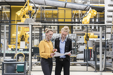 two women discussing plan in factory