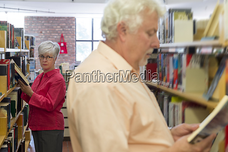 senior woman watching man reading book