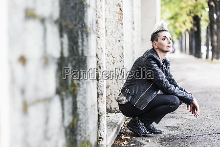 punk woman crouching at a building