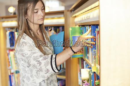 young woman choosing books at the
