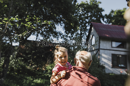 grandfather carrying granddaughter in garden