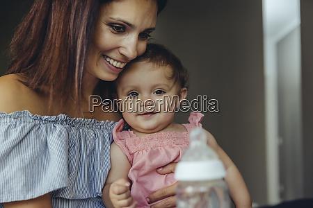 mother offering her baby girl milk