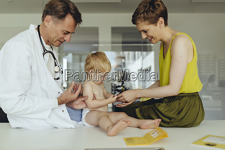 pediatrician vaccinating toddler injecting infants arm