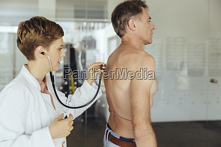 female doctor examining patient with a