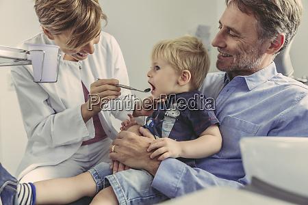 female dentist examining little boy sitting