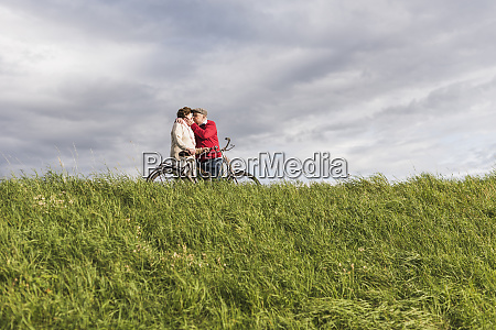 senior couple with bicycles kissing in