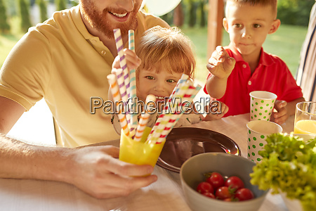 children taking straws a garden party