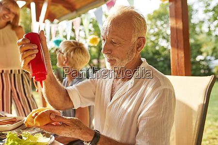 senior man preparing a hot dog